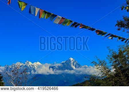 Colorful Tibetan Prayer Flag With Snow Clad Mountains In The Background Looking Beautiful With The L