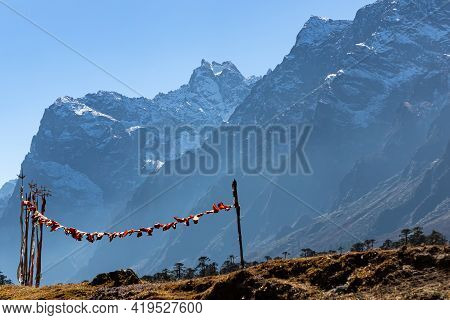 Tibetan prayer flags blowing with the wind with high mountain ranges in the background back lit with