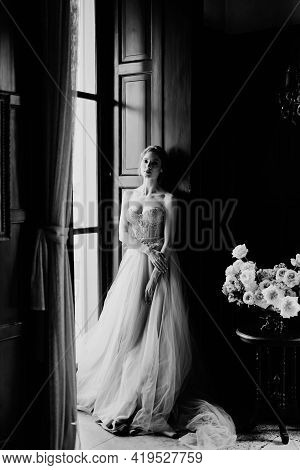 Bride Is Leaning Against The Frame Of The Large Window Of An Old Villa. Lake Como. Black And White P