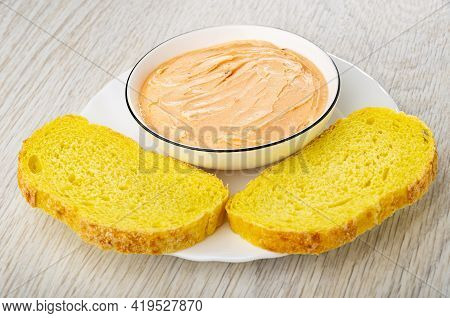 White Glass Bowl With Creamy Fish Oil, Slices Of Cornbread In Plate On Wooden Table