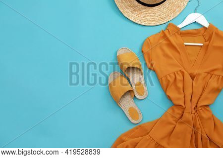 Dress, Straw Hat And Shoes On Light Blue Background, Flat Lay With Space For Text. Clothes Rent Conc