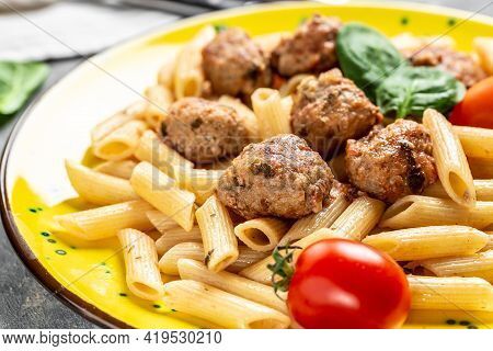 Penne Pasta With Meatballs And Tomato Sauce, On A Yellow Plate And A Gray Background.