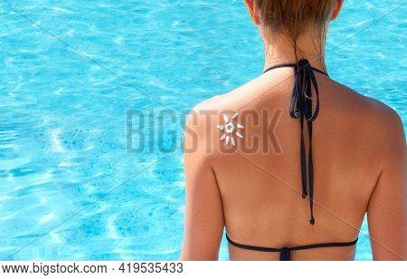 Woman Applying Sun Cream On Tanned  Shoulder In Form Of The Sun. Sun Protection.sun Cream. Skin And