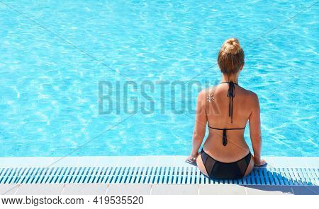 Young Woman Sitting On The Ledge Of The Pool.  Sun Protection. Sun Cream. Skin And Body