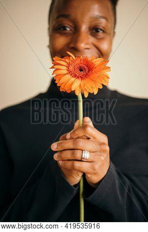 Happy black woman holding a daisy flower