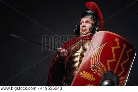 Clumsy Roman Soldier Points His Sword Against Dark Background