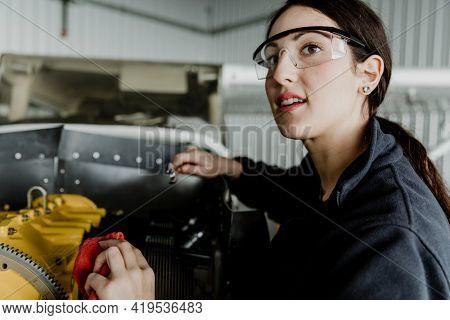 Female aviation technician repairing the motor of a propeller plane