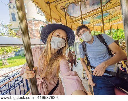 Man And Woman Wearing A Medical Mask During Covid-19 Coronavirus At An Amusement Park