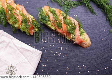 Delicious Canapes With Avocado And Smoked Salmon Fillet And Fresh Dill Sprigs And Sprinkled With Ses