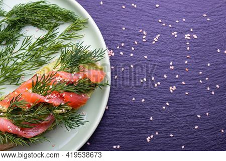 On A Plate Of Canapes - A Crispy Slice Of Baguette, Avocado And Smoked Salmon With Fresh Dill And Se