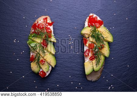 Two Slices Of Baguette With Slices Of Fresh Avocado And Slices Of Ripe Tomato, Sprinkled With Sesame