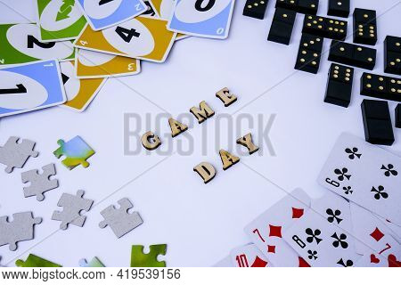 Kiev, Ukraine - 10.03.2021 Text Game Day. Dominoes Puzzles Playing Cards Around. The Concept Of Rela