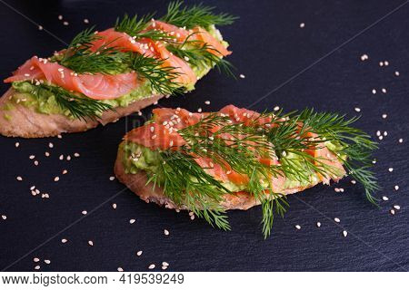 Two Mouth-watering Crispy Canapes With Avocado And Smoked Salmon Fillet And Fresh Dill Sprigs And Sp