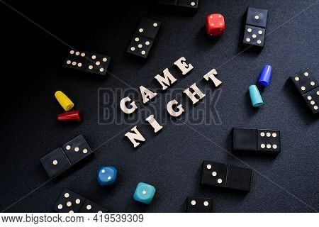 Text Game Night Spelled Out In Wooden Letter. Surrounded By Dice, Dominoes Other Game Pieces On Blac