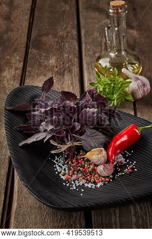 Purple Basil With Condiments And Oil On Wooden Table