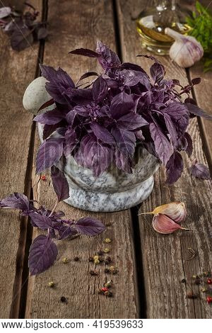 Purple Basil In Stone Mortar With Condiments On Wooden Table