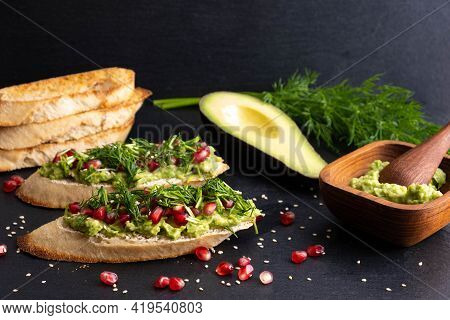 Canapes Of Avocado And Ripe Pomegranate Seeds, Sesame Seeds And Aromatic Dill, On A Black Background