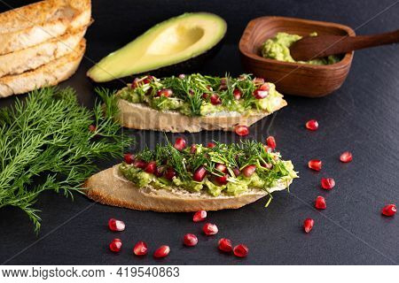 Canapes - Avocado, Ripe Pomegranate Seeds, Sesame Seeds And Aromatic Dill, On A Black Background, Cl