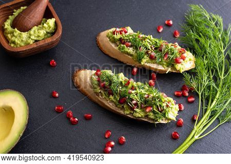 Delicious Avocado Canapes Sprinkled With Ripe Pomegranate Seeds, Sesame Seeds And Fragrant Fresh Dil