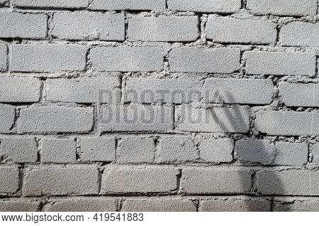 A Rough Dirty Gray Brick Wall With An Unusual Hand Shadow. An Elongated, Curved Shadow. The Sloppy M