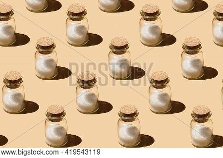 A Hard Light Pattern Of A Glass Jar With Cork Lids Containing Coarse Sea Salt On Pastel Yellow Seaml