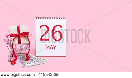 26th Day Of May. A Gift Box In A Shopping Trolley, Dollars And A Calendar With The Date Of 26 May On