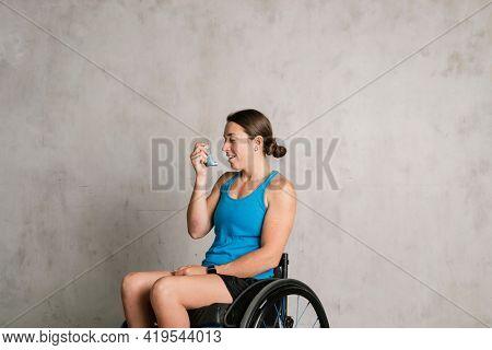 Woman in a wheelchair using an asthma inhaler