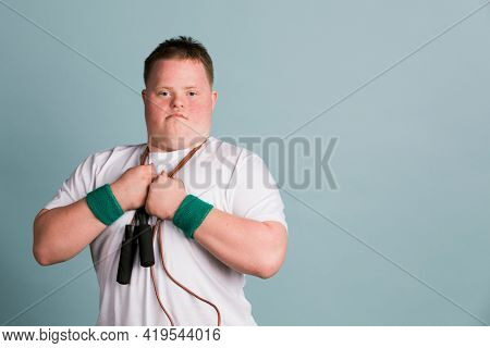 Proud kid with down syndrome holding a skipping rope around his neck
