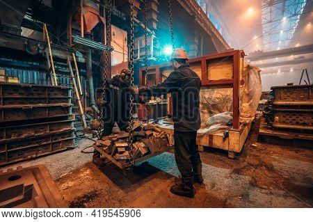 Heavy Industry Workers In Steel Mill Foundry Workshop Interior, Safety At Work And Teamwork In Metal