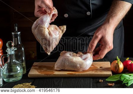 Preparing For Cooking Chicken Legs In The Restaurant Kitchen. The Chef Or Cook Is Holding Raw Chicke