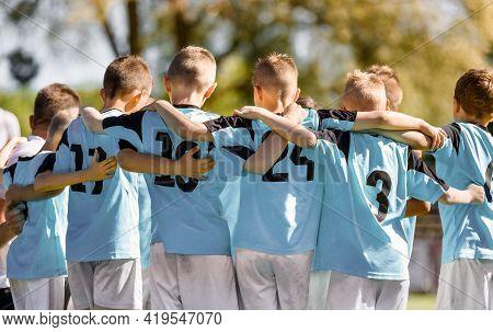 Kids Team Members In Sport Team. Happy Boys Huddling In Football Team. Children Standing In A Circle