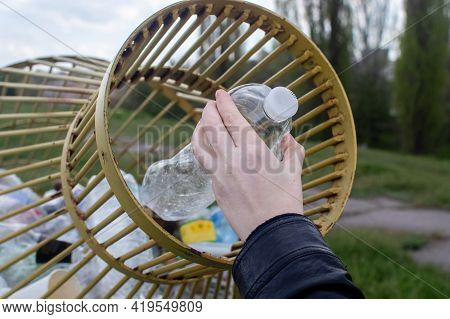 A Woman Tosses A Plastic Bottle Into A Plastic Container For Collection. Recycling And Disposal Of P