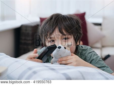 Kid Lying On Sofa Looking At Camera With Smiling Face, Cute Boy Laying Down On Couch Holding Remote,
