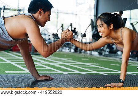 Healthy Smiling Couple Of Man And Woman Giving High Five To Each Other While Pushing Up In The Fitne