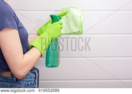 Woman In Gloves Holds Detergent And Cleaning Rag In The Bathroom