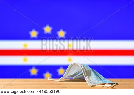 A Medical Mask Lies On The Table Against The Background Of The Flag Of Cape Verde. The Concept Of A