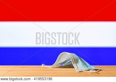 A Medical Mask Lies On The Table Against The Background Of The Flag Of The Netherlands. The Concept