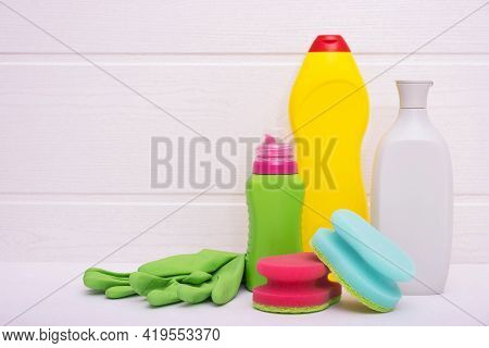 Colored Bottles With Liquid For Cleaning The House, Colored Rags And Green Gloves On A White Backgro