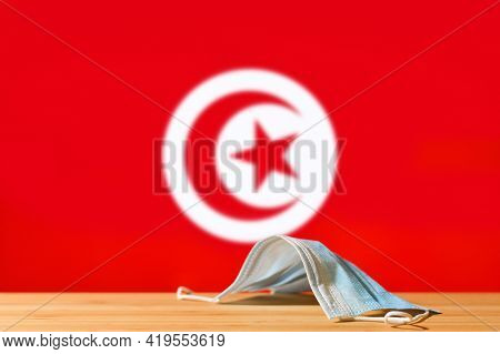 A Medical Mask Lies On The Table Against The Background Of The Flag Of Tunisia. The Concept Of A Man
