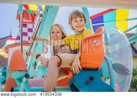 Happy Smiling Son And His Mother Spending Fun Time Together At Amusement Park