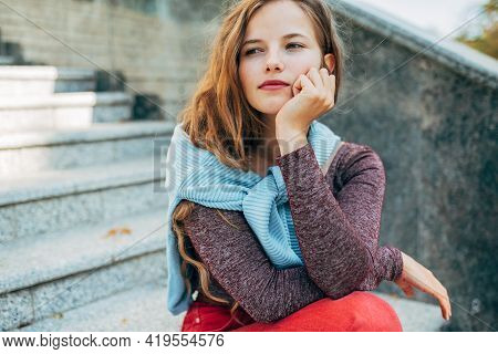 Candid Portrait Of A Pensive Female Takes A Rest Outside On The Street. Thoughtful Young Student Wom