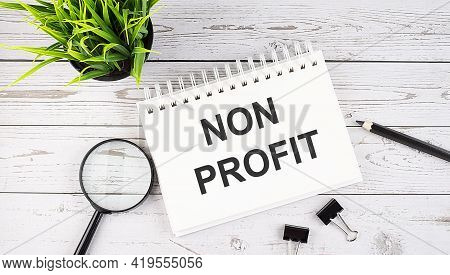 Non Profit Text Concept Write On Notebook With Office Tools On Wooden Background