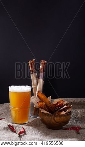 Jerky Snacks, Meat Sticks, Red Papper And Glass Of Beer On Burlap Cloth On Black Background With Cop