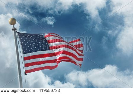 Flag of the United States of America over blue sky white clouds background