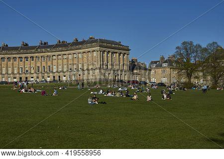 Bath, United Kingdom - April 25, 2021: Royal Crescent In Bath, Somerset, United Kingdom. People Sitt