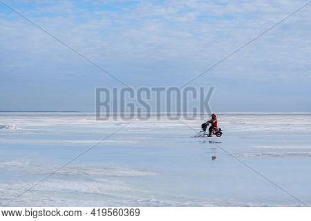 Saint Petersburg, Russia-march 27, 2021: Lonely Fisherman In Red Winter Outfit Is Coming Back From T