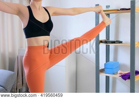 Young Slim Woman In Sportswear Is Doing Balancing Yoga Pose At Home Lifting Leg In Side, Body View.