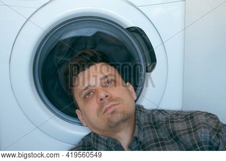 Tired Man Is Waiting The Washing Machine With Grey Bedspread Inside It, Doing His Laundry At Home Or