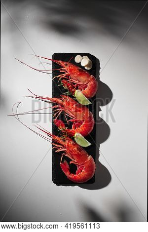 Three Red Prawns With Condiments On Grey Background With Shadow