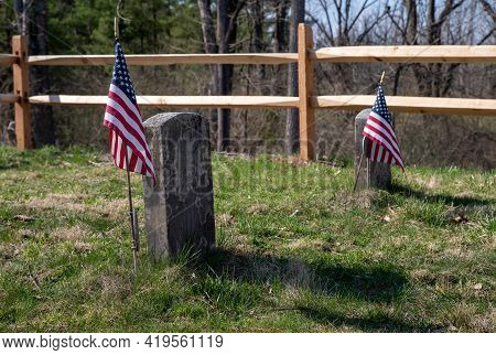Two Revolutionary War Soldiers Tombstones In Grassy Nature Setting Background, Fence And Flags.